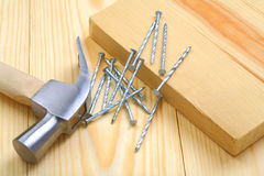 Claw hammer with nails and timber on table Stock Images