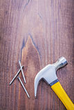 Claw hammer nails on vintage wooden board with Stock Photo