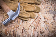 Claw hammer pair of leather safety gloves on chipboard Royalty Free Stock Photos