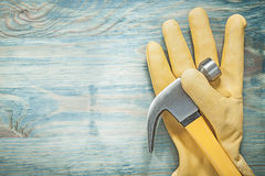 Claw hammer pair of leather safety gloves on wooden board constr Stock Photos