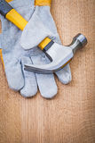 Claw hammer and protective glove on wooden board Royalty Free Stock Photography