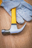 Claw hammer and protective glove on wooden board Stock Images