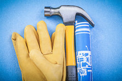 Claw hammer protective gloves rolled up construction drawings on Stock Photo