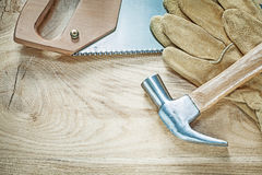 Claw hammer safety gloves stainless hacksaw on wooden board cons Stock Photo