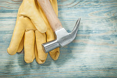Claw hammer yellow protective gloves on wood board construction Royalty Free Stock Photography