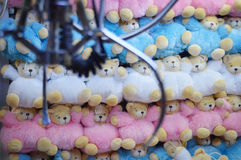 Claw Machine - Soft Toys. Light blue, pink and white animal soft toys inside the glass container with the electronic claw blurred in the foreground on the left Stock Image