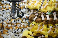 Claw Machine - Soft Toys. Various animal soft toys inside the glass container with the claw top left corner. At an arcade entertainment center Stock Photo