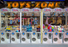 Claw machines on fun fair. GRONINGEN, THE NETHERLANDS-MAY 17, 2015: Claw crane Arcade machines with cuddly toys and teddy bears in bright colors on a fun fair Stock Photos