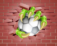 Claw with Soccer Ball Breaking Through Brick Wall Stock Images