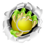 Claw with Tennis Ball Breaking out Of Background Royalty Free Stock Images