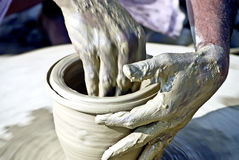 Clay. A clay goods manufacturer works on a thrower to make terracotta vases Stock Image