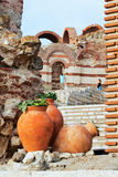 Clay amphora with plants. Large pitchers with the plants against the remnants of the ancient church Stock Photos