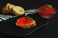 Appetizing sandwich with red salmon caviar on black ceramic plate, white baguette on paper napkin with geometric pattern and glass royalty free stock photos