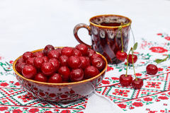 Clay bowl and cup with cherry. Clay bowl and cup with fresh cherry berries Stock Photo