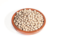 Clay bowl filled with chickpeas, isolated on white Stock Photography