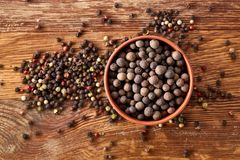 Clay bowl with pimento and peppercorns on vintage wooden background, top view, close-up, macro, selective focus. Some copy space for your text. Exotic asian stock images