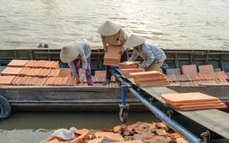 Clay bricks are transported into the boat, Mekong Delta, Vietnam Stock Photos