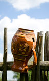 Clay broken pitcher hang on wooden woven fence Royalty Free Stock Photography