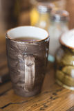 Clay brown cup of dark filtered coffee on wooden rustic table Royalty Free Stock Image
