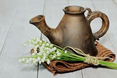 Clay brown teapot of unusual exclusive shape with bouquet of lilies of the valley tied with twine on rough light brown jute napkin royalty free stock photography