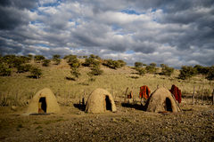Clay build round huts and wooden fence, Africa Stock Photography