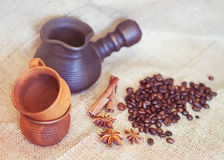 Clay cezve, cups, coffee beans and spices; selective focus. Toned image Royalty Free Stock Images