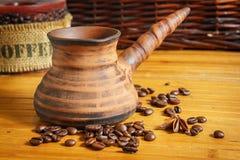 Clay Cezve Kaffeebohnen auf der hölzernen Tabelle Lizenzfreie Stockbilder