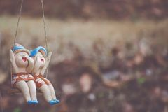 Clay child dolls sitting on swings in home, Concept of decoration. Royalty Free Stock Images