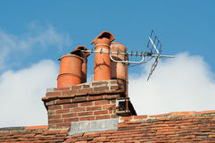 Clay chimney pots on old tiled roof. Old clay chimney pots and brick chimney stack on old tiled roof complete with TV aerial Royalty Free Stock Photography