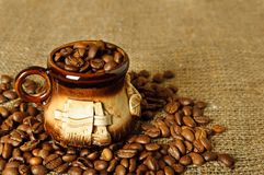 Clay coffee cup. With beans on the sack background, shallow depth of field Royalty Free Stock Images