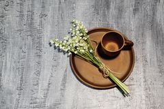 Clay coffee cup and bouquet of fragrant forest lilies of the valley tied with thin jute twine on ceramic dish. Dark concrete backg stock photo