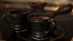Clay coffee set Cezve and two cups with steaming coffe. 