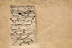 Clay-colored wall. With mudbrick in a window frame Royalty Free Stock Photos