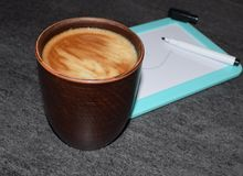 Photo of a cup of coffee on a background of a magnetic board and felt-tip pens. A saturated coffee color with an airy foam and a b stock photography