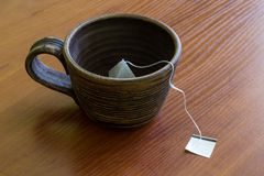 Clay cup with teabag. Brewing tea in a clay bowl on wood background Stock Images