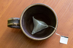 Clay cup with teabag.  Top view. Brewing tea in a clay bowl on wood background Stock Photos