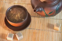 Clay cup and teapot with green tea and cane sugar cubes on a bamboo mat. Composition of a tea ceremony stock photography