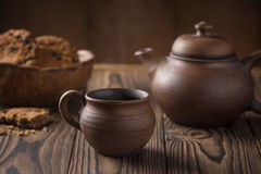 Clay cup with a teapot and a plate with biscuits on a wooden table Stock Photos