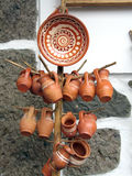 Clay cups. Traditional romanian clay pots and a plate on a wooden stand Royalty Free Stock Photos