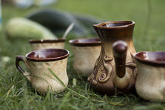 Clay cups and kitchenware on green grass. Closeup picture stock photos