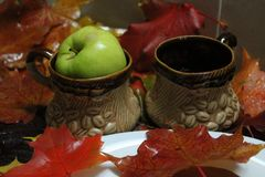 Coffee. Clay cups for morni g coffee on breakfast decorated green apples and bright autumn foliage stock images