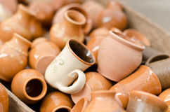 Clay cups and vases. A stack of glazed and unglazed terracotta earthenware cups and vases stock image