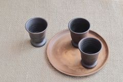 Clay dark brown wine glasses and a round earthen plate on a rough homespun background. royalty free stock photos