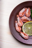 Clay dish with shrimp. On a wooden table is a plate with shrimp, lemon and herbs Stock Photo