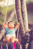 Clay doll on a swing Royalty Free Stock Images