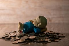 Clay doll on Thai coin pile. Wood background stock images