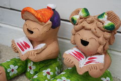 Clay doll. Twin clay doll smile and reading Stock Photo