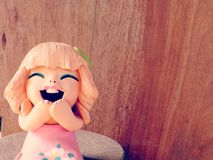 Clay dolls children girl smiling and laughing on wooden background Royalty Free Stock Photo