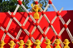Clay dolls on some Parallelograms structure of wooden sticks tied with red ropes and a red background royalty free stock images