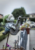 A clay elf play guitar. A little elf clay play guitar and seems a scarecrow for his small vase of flowers Stock Images